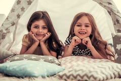 Little girls playing. Two cute little girls are looking at camera and smiling while playing together in child`s teepee Royalty Free Stock Images