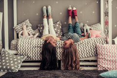 Little girls playing. Two cute little girls are looking at each other and smiling while lying on their backs on bed in children`s room Stock Photography