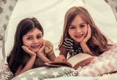 Little girls playing. Two cute little girls are reading a book, looking at camera and smiling while playing together in child`s teepee Stock Photography