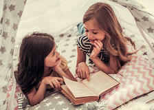 Little girls playing. Two cute little girls are reading a book and smiling while playing together in child`s teepee Royalty Free Stock Photography