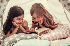 Little girls playing. Two cute little girls are reading a book and smiling while playing together in child`s teepee Stock Photography