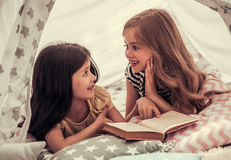 Little girls playing. Two cute little girls are reading a book and smiling while playing together in child`s teepee Royalty Free Stock Photo