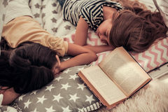 Little girls playing. Two cute little girls are sleeping after reading a book Royalty Free Stock Images