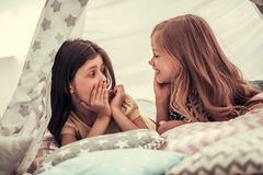 Little girls playing. Two cute little girls are talking and smiling while playing together in child`s teepee Royalty Free Stock Photos