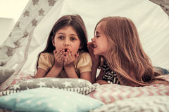 Little girls playing. Two cute little girls are talking and smiling while playing together in child`s teepee Royalty Free Stock Images