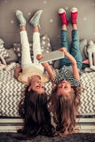 Little girls playing. Two cute little girls are using a digital tablet and smiling while lying on their backs on bed in children`s room Stock Photography