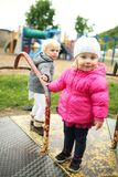 Little Girls Playing on a Vintage Merry-go-Round Outside on the. Two little toddler girls are playing oute on a merry-go-round at a playground on a cold fall day royalty free stock photo