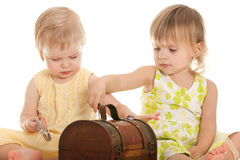 Little girls playing with a wooden chest Stock Photography