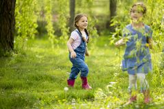 Little girls playuing in the forest stock image