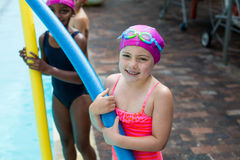 Little girls with pool noodles at poolside royalty free stock images