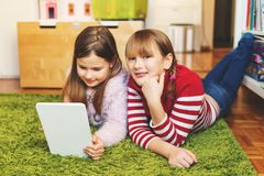 Little girls portrait. Two cute little girls playing on digital tablet pc, laying on green carpet in kid`s room Stock Images