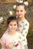 Little girls pose on floral blossom in spring garden. Sisters enjoy spring day outdoor. Children with blossoming flowers. Family, love and trust concept royalty free stock images
