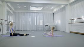 Little girls practice with teacher in ballet studio. Two children sit on gymnastic mat and raise their legs, copying movements of woman located opposite them stock video