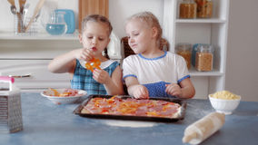 Little girls preparing pizza from ingredients royalty free stock photography