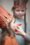 Little girls preparing to play Indians. Two sisters dressed as Indians. Mother painting face of her daughter Stock Photography