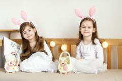 Little girls in rabbit ears sit on the couch with Easter baskets. Two cute little girls in rabbit ears are sitting on the sofa with Easter baskets Stock Photos