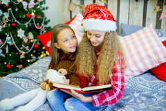 Little girls read book, Christmas time stock photo
