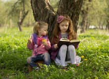 Little girls read book. One little girl reads book and other little girl eats apple Royalty Free Stock Photo