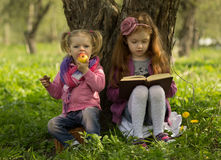 Little girls read book. One little girl reads book and other little girl eats apple Royalty Free Stock Photos