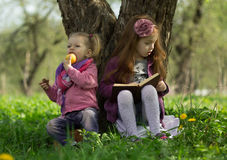 Little girls read book. One little girl reads book and other little girl eats apple Royalty Free Stock Images
