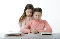 Little girls read books at the table on white Stock Image