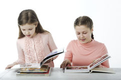 Little girls read books at the table on white Stock Photos