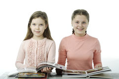 Little girls read books at the table on white Royalty Free Stock Photo