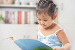 Little girls reading book. Little Asian girls reading book at home or library Stock Photo