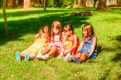 Little girls reading a book in the park Royalty Free Stock Image