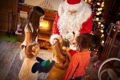 Little girls receiving Christmas presents Stock Photos