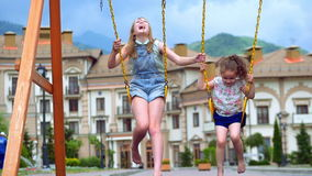 Little girls ride on a swing. Two little sisters enjoy life on the swings. stock video footage