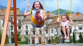 Little girls ride on a swing. Two little sisters enjoy life on the swings. Little girls ride on a swing. Children on a Swing. 4k stock video