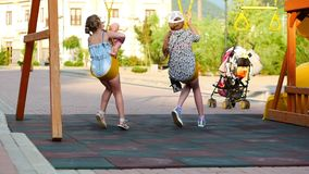 Little girls ride on a swing. Two little sisters enjoy life on the swings. Little girls ride on a swing. Two little sisters enjoy life on the swings stock footage