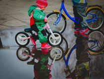Kids riding bike in spring water puddle. Little girls riding bike in spring water puddle, seasonal activities for kids royalty free stock images