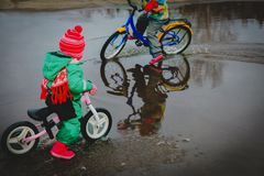Kids riding bike in spring water puddle. Little girls riding bike in spring water puddle, seasonal activities for kids royalty free stock image