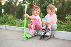 Little girls with roller, scooter seat. Two little girls with roller, scooter seat on border Royalty Free Stock Photo