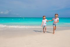Little girls running along the white beach and having fun Royalty Free Stock Photos