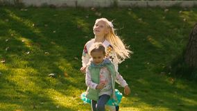 Little girls running in green park and enjoying their play stock video footage