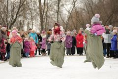 Little girls sack-racing during winter Maslenitsa carnival in Ru Royalty Free Stock Images