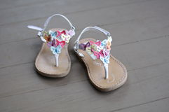 Little Girls Sandals. A little girls sandals sit on a wooden floor and shine in the morning sun Royalty Free Stock Photography
