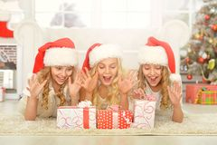 Little girls in Santa hats. Portrait of three cute little girls in Santa hats lying on the floor royalty free stock image