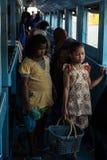 Little girls selling snacks on ferry boat stock image