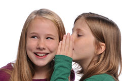 Little girls sharing a secret. Isolated on a white background royalty free stock photos