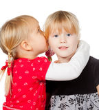 Little girls sharing a secret. Portrait of little girl telling a secret to her friend over a white background stock photo