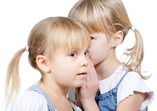 Little girls sharing a secret. Portrait of little girl  telling a secret to her friend over a white background Royalty Free Stock Photos