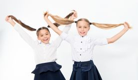 Little girls show long hair tails. School children. Happy children enjoy healthy hair. Hairdressing is our passion stock photos