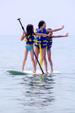 Little girls show off on paddle board Royalty Free Stock Photography