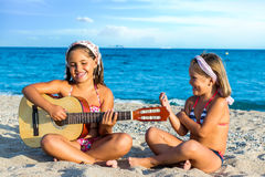 Little girls singing with guitar on beach. Close up portrait of two little girls singing together with guitar on beach Royalty Free Stock Photo