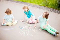 Little sisters draw with color chalk outdoors. Chalk drawings. royalty free stock images