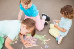 Little sisters draw with color chalk outdoors. Chalk drawingsю stock image